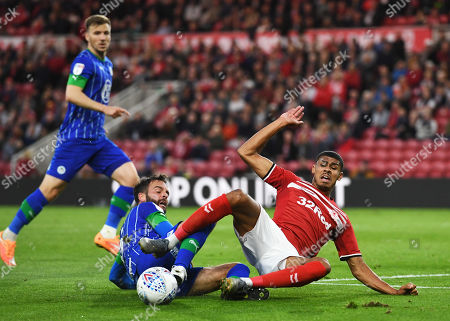 Ashley Fletcher of Middlesbrough (right) is brought down in the penalty box by Danny Fox of Wigan Athletic but no penalty kick is given by the referee