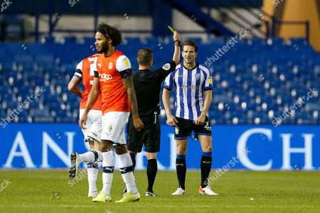 Referee David Webb issues a yellow card to Sam Hutchinson of Sheffield Wednesday during the EFL Sky Bet Championship match between Sheffield Wednesday and Luton Town at Hillsborough, Sheffield