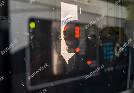 China's Xie Zhenhua, center, and Chile's Environment Minister Carolina Schmidt, left, are reflected in glass on a control panel as they visit the Quilapilún solar plant, a joint venture by China and Chile, in Colina, Chile, . Chile is highlighting their alliance with China to push for a global call to reduce global warming ahead of the global climate change summit in Santiago next December