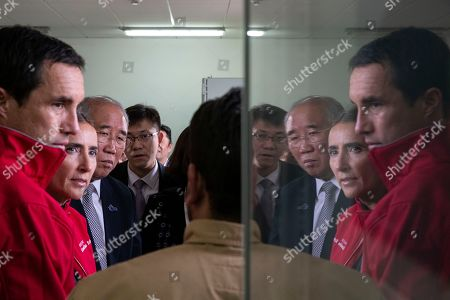 Stock Image of Chile's Energy Minister Juan Carlos Jobet, left, Chile's Environment Minister Carolina Schmidt, second from left, and China's Xie Zhenhua, third from left, are reflected in glass during their tour of the Quilapilún solar plant, a joint venture by China and Chile, in Colina, Chile, . Chile is highlighting their alliance with China to push for a global call to reduce global warming ahead of the global climate change summit in Santiago next December