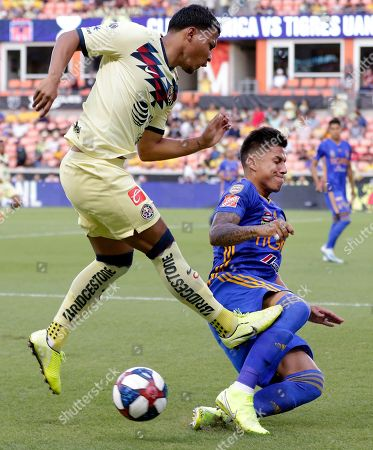 Club America's Roger Martinez, left, jumps to avoid hitting Tigres' Carlos Salcedo, right, during the first half of a UANL Leagues Cup semifinal, in Houston