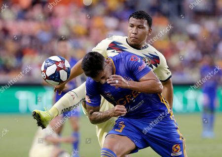 Tigres' Carlos Salcedo (3) ducks to avoid the kick by Club America's Roger Martinez, back, during the first half of a UANL Leagues Cup semifinal, in Houston