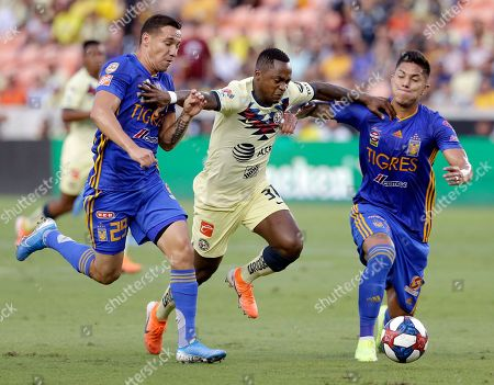 Club America's Renato Ibarra, middle, tries to hold back Tigres' Jesus Duenas (29) and Carlos Salcedo as they chase the ball during the first half of a UANL Leagues Cup semifinal, in Houston