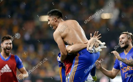 Tigres' Carlos Salcedo, shirtless, celebrates with his teammates after kicking the winning goal during the tie breaker against Club America during the second half of a UANL Leagues Cup semifinal, in Houston