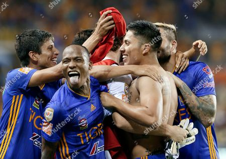Tigres' Carlos Salcedo, shirtless, celebrates with his teammates after kicking the winning goal during the tie-breaker against Club America during the second half of a UANL Leagues Cup semifinal, in Houston