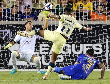 Club America's Andres Ibarguen (11) kicks in a goal over Tigres' Carlos Salcedo (3) as goalie Nahuel Guzman, left, only deflects the ball into the net during the second half of a UANL Leagues Cup semifinal, in Houston