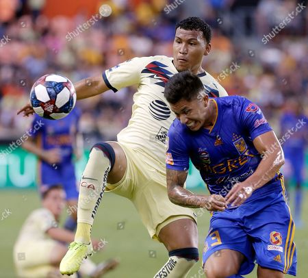 Roger Martinez, Carlos Salcedo. Club America's Roger Martinez, left, jumps to kick the ball as Tigres' Carlos Salcedo braces for contact during the first half of a UANL Leagues Cup semifinal, in Houston