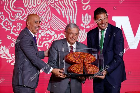 President of Mexico Andres Manuel Lopez Obrador, receives recognition from the Chairman of the Board of Directors of Grupo Financiero Banorte Carlos Hank Gonzalez (R), and the CEO Marcos Ramirez (L) during the Banorte Strategy Forum, in Mexico City, Mexico, 21 August 2019. The Mexican economy has slowed more than expected and has widened the gap between its potential and real growth, Mexico's central bank governor Alejandro Diaz de Leon said during an economic forum in the capital.