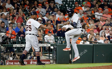 Detroit Tigers' Ronny Rodriguez, right, celebrates with third base coach Dave Clark (25) after hitting a home run against the Houston Astros during the fifth inning of a baseball game, in Houston