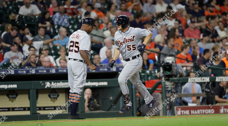 Detroit Tigers' John Hicks (55) celebrates with third base coach Dave Clark (25) after hitting a home run against the Houston Astros during the ninth inning of a baseball game, in Houston