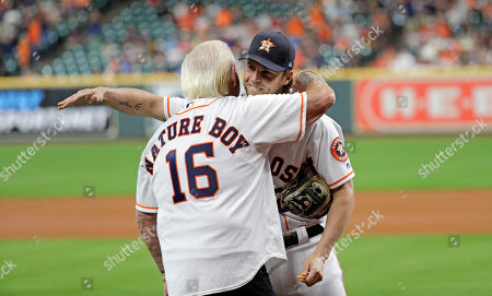 Former professional wrestler Richard Fliehr, left, hugs Houston Astros right fielder Josh Reddick after throwing out the ceremonial first pitch before a baseball game against the Detroit Tigers, in Houston