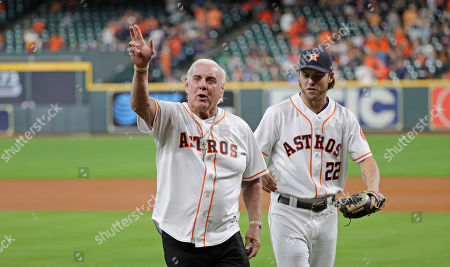 Former professional wrestler Richard Fliehr, left, greets Houston Astros right fielder Josh Reddick (22) after throwing out the ceremonial first pitch before a baseball game against the Detroit Tigers, in Houston