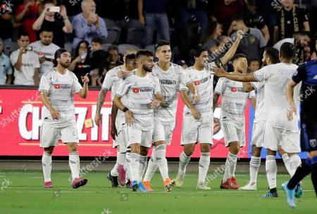 Los Angeles FC forward Carlos Vela, with arm raised, celebrates with teammates after scoring on a penalty kick against the San Jose Earthquakes during the first half of an MLS soccer match, in Los Angeles