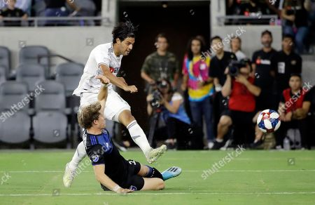 Carlos Vela, Florian Jungwirth. Los Angeles FC forward Carlos Vela, top, takes a shot on goal as San Jose Earthquakes midfielder Florian Jungwirth, bottom, defends during the second half of an MLS soccer match, in Los Angeles