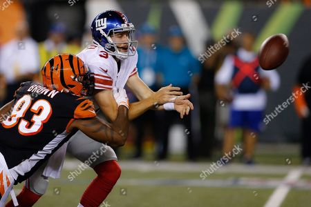 Cincinnati Bengals defensive end Andrew Brown (93) forces a fumble by New York Giants quarterback Alex Tanney (3) during the second half of an NFL preseason football game, in Cincinnati