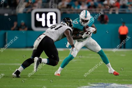 Jacksonville Jaguars defensive end Josh Allen (41) prepares to tackle Miami Dolphins running back Kalen Ballage (27) during the first half of an NFL football preseason game, in Miami Gardens, Fla