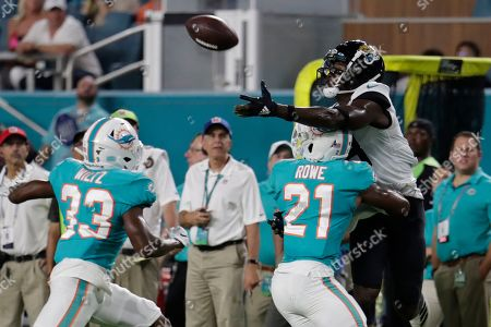 Chris Conley, Jomal Wiltz, Eric Rowe. Jacksonville Jaguars wide receiver Chris Conley, right, attempts to catch a pass as he is guarded by Miami Dolphins cornerback Eric Rowe (21) and cornerback Jomal Wiltz (33) during the first half of an NFL football preseason game, in Miami Gardens, Fla
