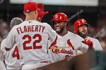 St. Louis Cardinals' Dexter Fowler, center, is congratulated by teammates Jack Flaherty (22) and Matt Carpenter, right, after hitting a two-run home run during the seventh inning of a baseball game against the Colorado Rockies, in St. Louis