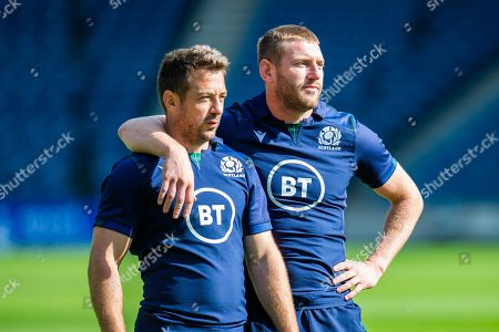 Stock Photo of Scotland team mates Greg Laidlaw (left) and Finn Russell watch a passing drill during the Scotland Rugby training run ahead of their match against France at BT Murrayfield Stadium, Edinburgh