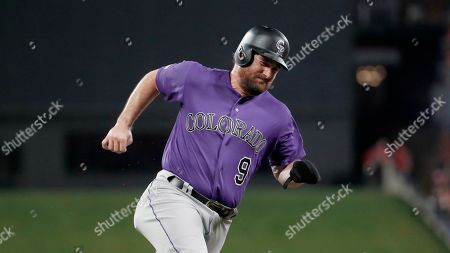 Colorado Rockies' Daniel Murphy rounds third and heads home to score during the second inning of a baseball game, in St. Louis