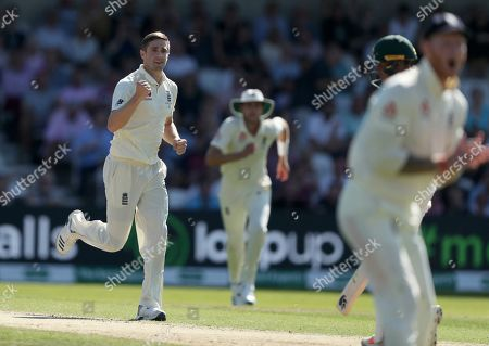 England's Chris Woakes celebrates after taking the wicket of Australia's Usman Khawaja caught by England's Jason Roy during play on the second day of the 3rd Ashes Test cricket match between England and Australia at Headingley cricket ground in Leeds, England