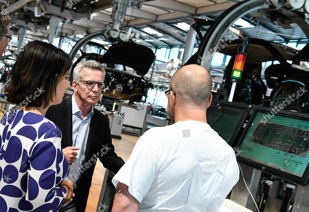 Stock Photo of Former German Interior Minister Thomas de Maiziere (C) and Germany's Greens party co-leader Annalena Baerbock (L) talk to an Volkswagen worker during their visit of the Volkswagen Transparent Factory prior to a panel discussion in Dresden, Germany, 23 August 2019.