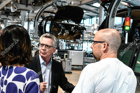 Former German Interior Minister Thomas de Maiziere (C) and Germany's Greens party co-leader Annalena Baerbock (L) talk to an Volkswagen worker during their visit of the Volkswagen Transparent Factory prior to a panel discussion in Dresden, Germany, 23 August 2019.