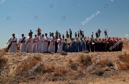 Stock Picture of Iraqi Christians attend Mass at the archaeological site of Kokheh Church south of Baghdad, Iraq, . The historical church located on the left bank of the Tigris River some 20 miles south of the capital Baghdad dates back to the first century AD. Remnants of the church, an archaeological site and one of the most important sites of Eastern Christianity, was reopened again to the public last year after a years-long closure due to security concerns