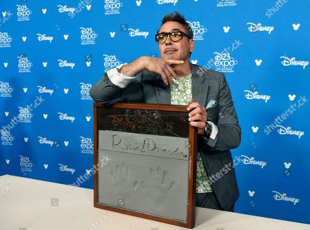 Robert Downey Jr. poses during his handprint ceremony at the Disney Legends press line during the 2019 D23 Expo, in Anaheim, Calif