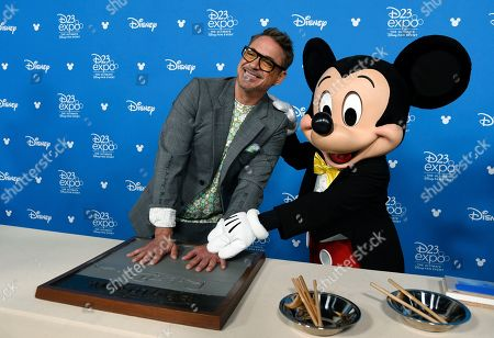 Robert Downey Jr. poses with Mickey Mouse during his handprint ceremony at the Disney Legends press line during the 2019 D23 Expo, in Anaheim, Calif