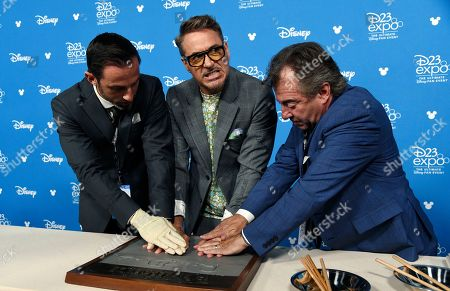Attendants help actor Robert Downey Jr., center, press his hands in cement during his handprint ceremony at the Disney Legends press line during the 2019 D23 Expo, in Anaheim, Calif