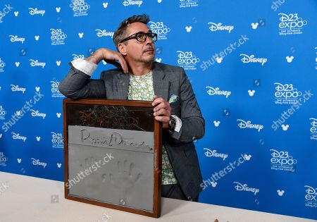 Robert Downey Jr. strikes a pose during his handprint ceremony at the Disney Legends press line during the 2019 D23 Expo, in Anaheim, Calif