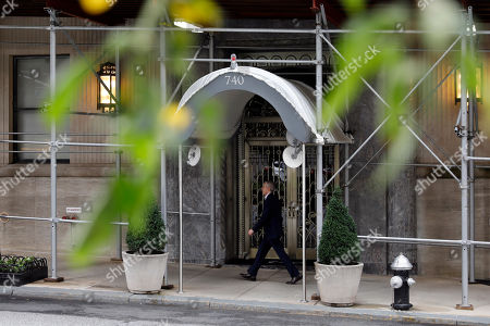 A man passes the Park Avenue residence of billionaire industrialist David H. Koch, in New York, . Koch, who with his older brother Charles, was both celebrated and demonized for transforming American politics by pouring their riches into conservative causes, died Friday at 79
