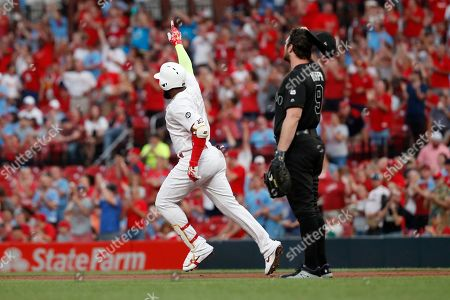 St. Louis Cardinals' Marcell Ozuna, left, celebrates as he rounds the bases past Colorado Rockies first baseman Daniel Murphy, right, after hitting a two-run home run during the first inning of a baseball game, in St. Louis