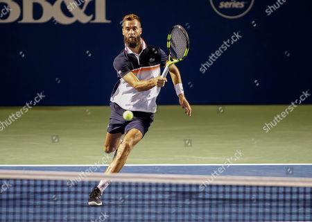 Benoit Paire, of France, hits a return in the third set against Steve Johnson in the Winston-Salem Open tennis tournament in Winston-Salem, N.C