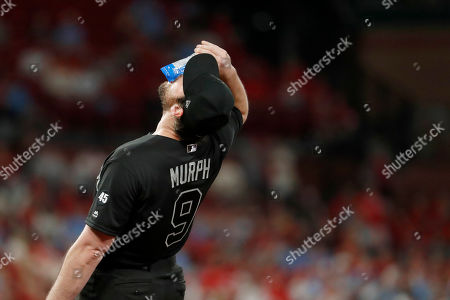 Colorado Rockies first baseman Daniel Murphy pours seeds into his mouth between pitches during the fifth inning of a baseball game against the St. Louis Cardinals, in St. Louis