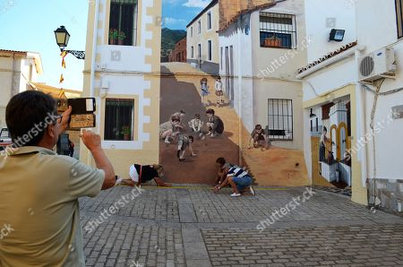 A man using a mobile phone takes a photo of several people enacting the scene of a mural picturing children playing with marbles, in the village of Romangordo, in Extremadura, western Spain, 24 August 2019. The village, with a population of 300, has managed to attract some 25,000 tourists, so far this year, with its 'Route of Trompe l'oeil' made up of several realistic murals painted in walls and the facades of houses.