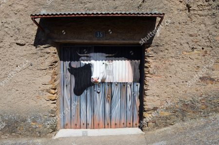 A view of a mural painted on the door of a house depicting a cow in its stable, in the village of Romangordo, in Extremadura, western Spain, 24 August 2019. The village, with a population of 300, has managed to attract some 25,000 tourists, so far this year, with its 'Route of Trompe l'oeil' made up of several realistic murals painted in walls and the facades of houses.