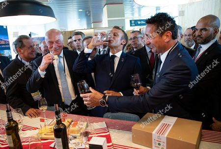 Stock Photo of French President Emmanuel Macron (C), flanked by President of the Nouvelle-Aquitaine region Alain Rousset (L) samples local produce and wine, as he tours the exhibition hall above the international press center on the opening day of the G7 summit, in Anglet, France, 24 August 2019. The G7 Summit runs from 24 to 26 August in Biarritz.