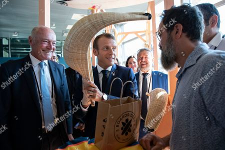 French President Emmanuel Macron (C), flanked by President of the Nouvelle-Aquitaine region Alain Rousset (L) is presented a Chistera, a wicker glove used in the traditional Basque pelota game, as he tours the exhibition hall above the international press center on the opening day of the G7 summit, in Anglet, France, 24 August 2019. The G7 Summit runs from 24 to 26 August in Biarritz.