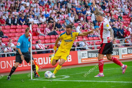 Luke O'Neill (#2) of AFC Wimbledon looks to cross the ball as Chris Maguire (#7) of Sunderland AFC appeals to the assistant referee during the EFL Sky Bet League 1 match between Sunderland and AFC Wimbledon at the Stadium Of Light, Sunderland