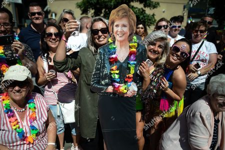 Stock Picture of Members of the watching crowd with a Cilla Black cutout