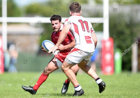 Rhodri Jones of Scarlets A is tackled by Graham Curtis.