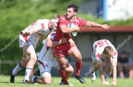 Rhodri Jones of Scarlets A is tackled by Zack McCall.
