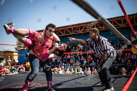 Wrestler from the SAPW South African Pro Wrestler 'Arachnida' carries 'Demi Rose' during a wrestling match at the Laerskool Morewag school in Johannesburg, South Africa, 24 August 2019. In the East Rand region of South Africa lives dedicated, passionate, amateur hardcore wrestling community, whose members find time between work and family to put on shows for their devoted following of fans at local community halls, high schools and motorcycle rallies. Hardcore wrestling is a form of professional wrestling where disqualifications, count-outs, and all other different rules do not apply. Matches are decided with the use of numerous dangerous items including tables, chairs, barbed wire, light tubes, shovels, chains, hammers, etc.