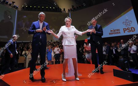 Stock Photo of Romanian Prime Minister Viorica Dancila (C), also the President of the leftist ruling party Social Democracy Party (PSD), flanked by her aides Mihai Fifor (R), party deputee president, and Eugen Orlando Teodorovici (L), the executive chairman of the PSD (and the finance minister), gestures on the stage during the party congress in Bucharest, Romania, 24 August 2019. Up to 1000 PSD party members from all over the country, gathered at the congress hosted by the Parliament House to nominate their candidate to run for the presidential election in November 2019. Dancila was nominated as PSD candidate for the 2019 presidential elections, that will be held in November 2019. The poster on the back writes: 'FOR ROMANIA PSD'.