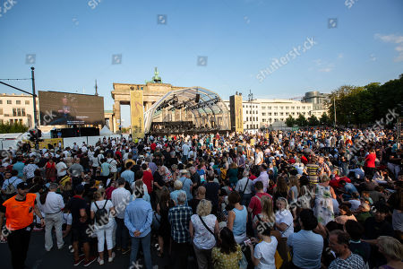 People gather in front of the Brandenburg Gate to watch The Berlin Philharmonic Orchestra (Berliner Philharmoniker), in Berlin, Germany, 24 August, 2019. The world famous orchestra will play for the first time in an open-air concert Beethoven's Ninth under a new leadership of Russian-Austrian conductor Kirill Petrenko, replacing conductor Simon Rattle.