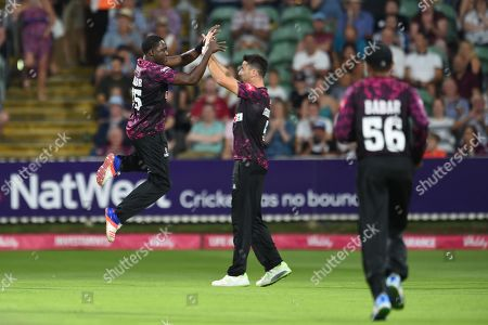 Jerome Taylor and Tim Groenewald of Somerset celebrate the wicket of Shaun Marsh during the Vitality T20 Blast South Group match between Somerset County Cricket Club and Glamorgan County Cricket Club at the Cooper Associates County Ground, Taunton