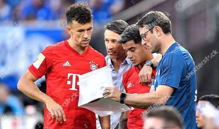 Bayern's manager Niko Kovac and his assistant coach Robert Kovac show their new players Ivan Perisic, left, and Philippe Coutinho the tactics before they are changed in during the German Bundesliga soccer match between FC Schalke 04 and Bayern Munich in Gelsenkirchen, Germany