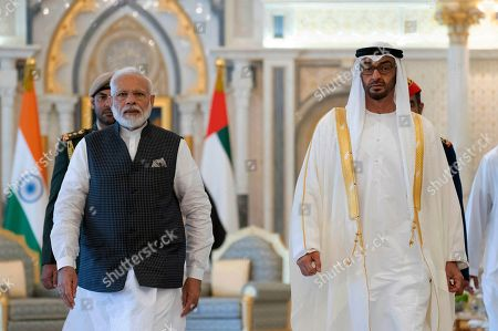 In this photograph made available by the state-run WAM news agency, Indian Prime Minister Narendra Modi, left, walks with Sheikh Mohammed bin Zayed Al Nahyan, right, in Abu Dhabi, United Arab Emirates, . Modi is on a trip to both the United Arab Emirates and Bahrain, reinforcing ties between India and the Gulf Arab nations as he pursues stripping statehood from the disputed Muslim-majority region of Kashmir